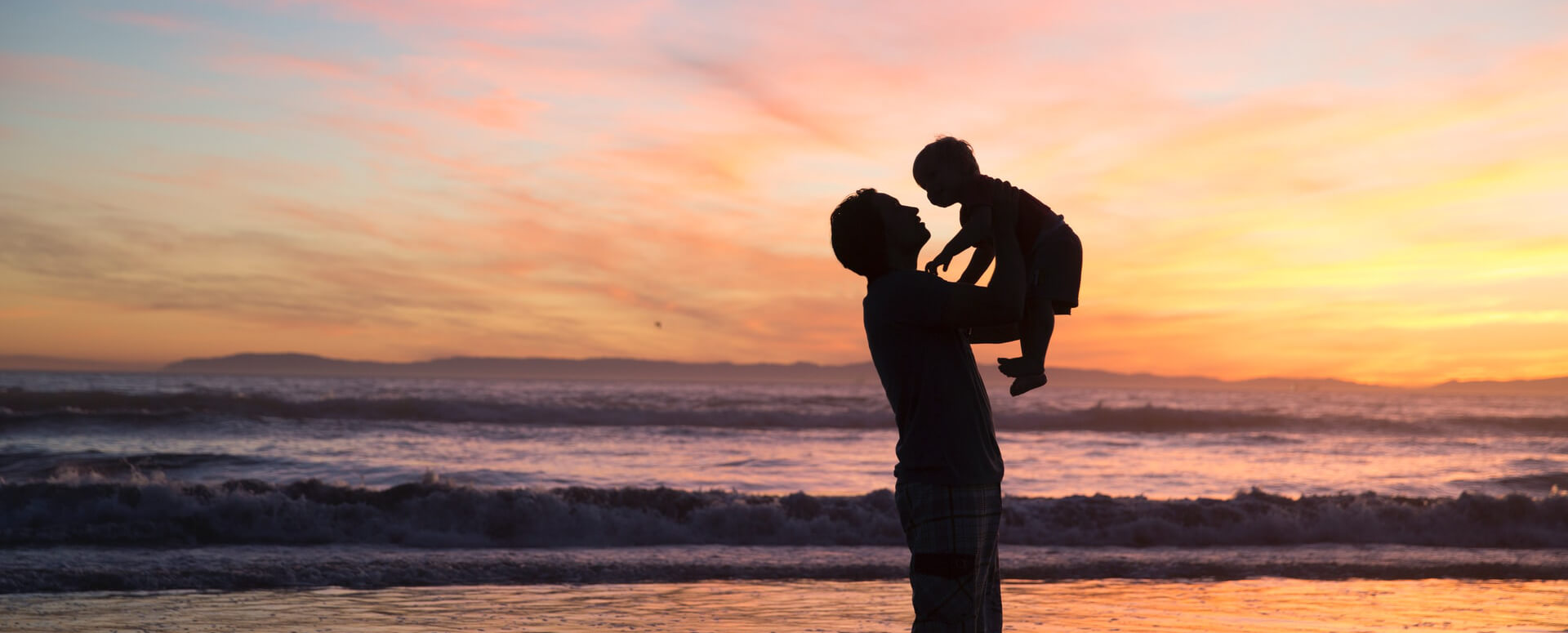 Father holding baby on beach
